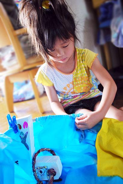 保育園の子どもたち、皆で染めた空色の布を、  「荒馬踊り」の自分の馬に、縫いつけています。