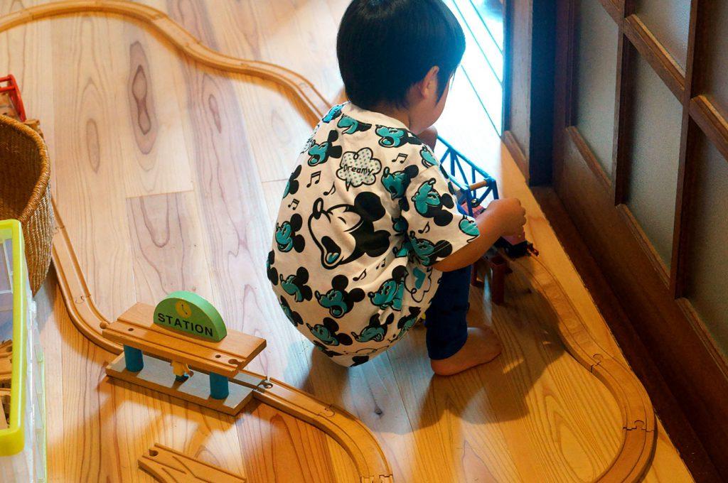 木製の線路を組み立てて遊ぶ子ども